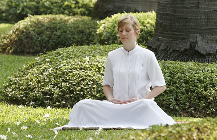 woman doing meditation in the grass